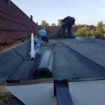 dakdekker bezig met het dak